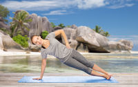 woman doing yoga in side plank pose on beach