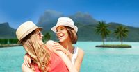 smiling young women in hats on bora bora beach