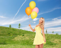 happy woman with helium air balloons in summer