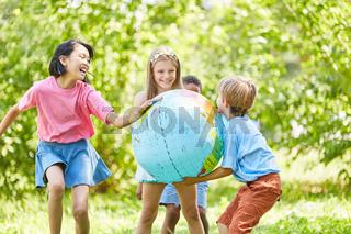 Kinder spielen im Sommer mit Weltkugel Ball