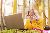 Close-up Toned image of a freelancer girl portrait in a yellow sweater and glasses looking thoughtfully at the laptop screen in the nature in a coniferous forest. The concept of freelancing freedom for travel and lack of binding to the office. A laptop li