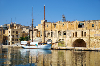 The yacht moored at the pier near the old dock. Malta.