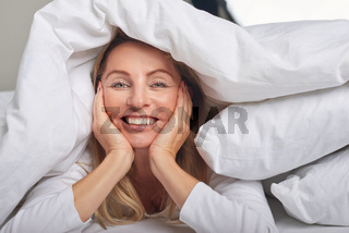 Beautiful middle-aged woman under sheets