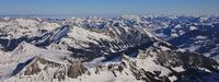 Frozen lake Arnensee and mountain ranges near Gstaad, Switzerland. View from glacier des Diablerets.