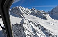 Blick aus einem Helikopter über verschneite Gipfel der Berner Alpen zur Lötschenlücke, Schweiz