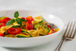 Whole farfalle pasta with zucchini, cherry tomatoes and red onion
