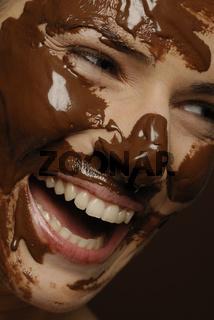 Junge Frau mir Schokolade im Gesicht