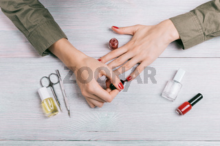 Woman making a manicure and paint fingernails in red