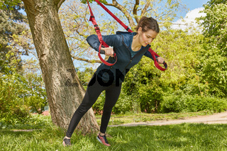 Frau bei Suspension Sling Training am Baum