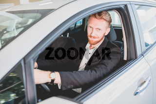 Young man sitting in new car in auto showroom.