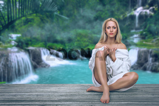 Young woman relaxing in resort spa in front of waterfall in tropical jungle
