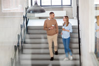 man and woman with coffee at office stairs