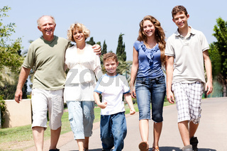 Extended family group walking down the pathway and looking at camera