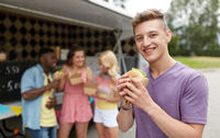 happy man with hamburger and friends at food truck