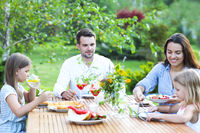 Happy family of four people enjoying meal together outdoors