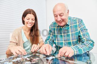 Junge Frau beim Puzzle spielen mit Senior