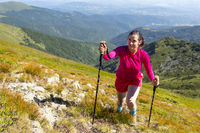 Young woman in pink trekking in the mountain