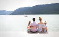 Young family of four sitting by lake