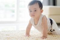 Chinese baby boy crawling on carpet.