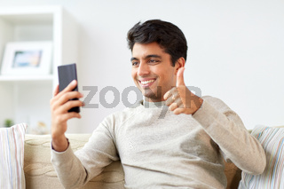 happy man having video call on smartphone at home