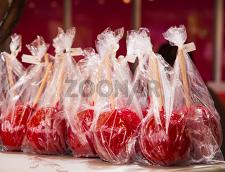 Red candy apples in plastic foil