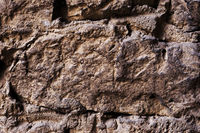 Close up Textured background of a wall of medieval stone masonry. The wall is sloppy built of mountain stones. Medieval style