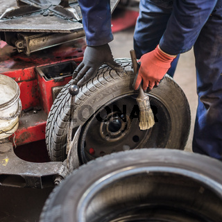 Professional auto mechanic replacing tire on wheel in car repair service.