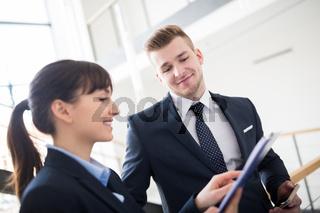 Junger Geschäftsmann und Kollegin mit einer Checkliste