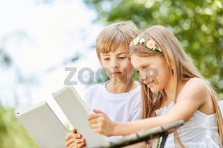 Zwei Kinder schauen neugierig auf Tablet