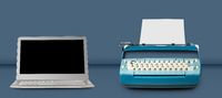 Old electric typewriter with laptop on blue table background