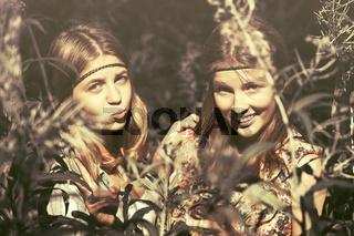 Two happy teen girls walking in summer forest