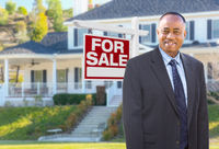 African American Agent In Front of Beautiful Custom House and For Sale Real Estate Sign.