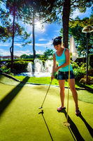 Mini Golf - Woman playing Golf on green grass at sunset