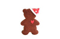 Gingerbread classic cookie in the form of a bear cub with a heart and a New Year's cap. Merry Christmas and happy New Year. Isolated.