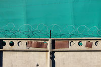 Barbed wire on an old concrete wall guards an object against a green awning