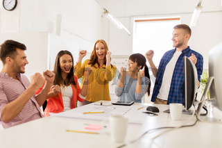 happy creative team celebrating success at office