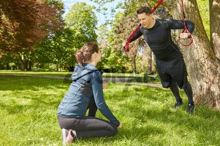 Mann bei Suspension Sling Training im Park
