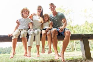 Familie und Kinder sitzen entspannt im Park