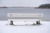 weiße Bank an einem See im Winter