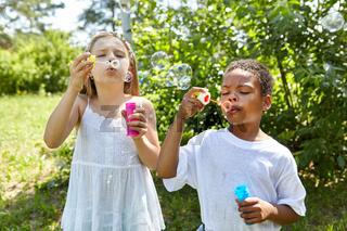 Mädchen und Junge pusten Seifenblasen zusammen