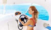 Young blond woman in bikini steering the sailing boat