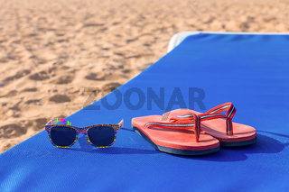 Slippers and sunglasses on sunbed at beach