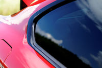 Detail on hot red sport car - fuel cap and window