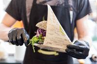 Chef serving organic vegetarian fish burger at international urban street food festival.