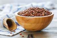 Dry brown lentils in a wooden bowl.