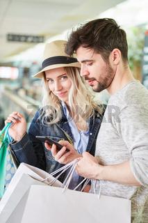Junges Paar mit Smartphone beim Shopping