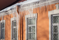 Long icicles hang from the edge of the roof. End of winter