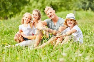 Glückliche Familie sitzt entspannt im Gras