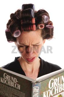 Hausfrau liest ratlos im Kochbuch