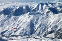 Paragliding at snow mountains over ski resort